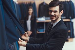 Smiling successful young man checks quality of jacket fabric in mens clothing store. Smiling successful young men checks quality of jacket fabric in mens Stock Photo