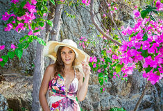 Smiling summer woman with hat at flowers Stock Image