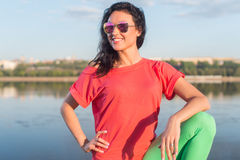 Smiling summer woman wearing sunglasses near river. Stock Photos