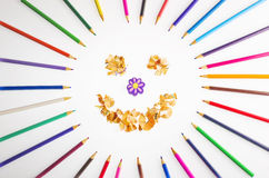 Smiling sun arranged from crayons and pencil sharpenings. Royalty Free Stock Images