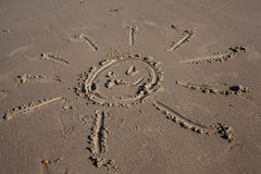 Smiling sun, drawn on the sand of a beach Royalty Free Stock Photography