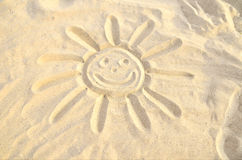 Smiling sun drawn in the sand. Sun symbol drawn in the sand, smiling face, smiley. yellow sand, sunny day Stock Images