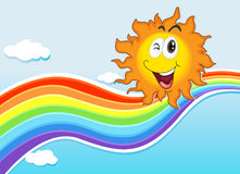 A smiling sun near the rainbow Stock Photo