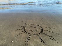 Smiling sun painted on the sand beach Stock Image