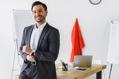 smiling super businessman standing near table and looking at camera stock photos