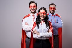 Smiling super businesspeople in masks and capes with crossed arms. On grey royalty free stock photo