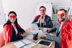 smiling super businesspeople in masks and capes sitting at table royalty free stock photography