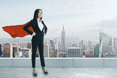 Confidence and leadership concept. Smiling super hero woman with red cape standing on rooftop with city view and daylight. Confidence and leadership concept stock photos