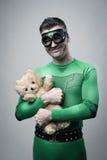 Smiling superhero cuddling a teddy bear Royalty Free Stock Image