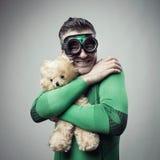 Smiling superhero cuddling a teddy bear Stock Photos