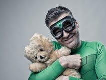 Smiling superhero cuddling a teddy bear Royalty Free Stock Photography