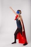 Smiling superhero female raised her hand up Stock Image
