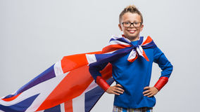 Smiling superhero. Smiling funny super hero boy posing with arms akimbo and wearing a British flag as a cape royalty free stock photos