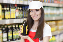 Smiling Supermarket Employee Holding a Product. Portrait of a young sales clerk in a market store royalty free stock image