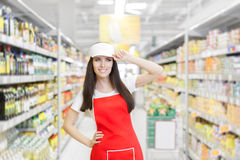Smiling Supermarket Employee Standing Among Shelves. Portrait of a young sales clerk in a market store stock image