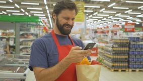 Smiling supermarket employee using mobile phone and holding shopping bag in supermarket. Supermarket employee using mobile phone and holding shopping bag in stock video