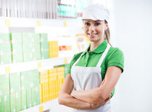 Smiling supermarket worker with shelf on background Stock Images