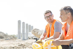 Smiling supervisor sitting with colleague at construction site Royalty Free Stock Photography