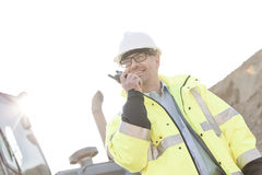 Smiling supervisor using walkie-talkie at construction site against clear sky Stock Photography