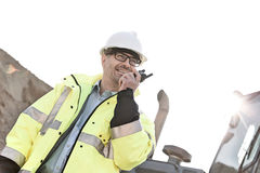 Smiling supervisor using walkie-talkie at construction site against clear sky Stock Images
