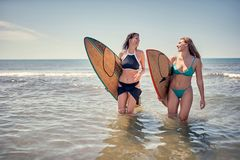 Smiling Surfer girl walking with board on the sandy beach. Surfer girl. Beautiful young woman at the beach. water sports. . royalty free stock photo