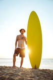 Smiling surfer holding surf board while standing at the beach. Smiling young surfer holding surf board while standing at the beach at sunset Stock Photos