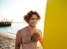 Smiling surfer holding surf board while standing at the beach. Smiling young surfer holding surf board while standing at the beach at sunset Royalty Free Stock Photos