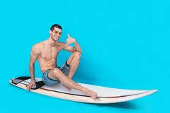 Cheerful surfer showing call me sign. Smiling surfer man showing call me sign, posing in studio on blue background, sitting on the board with naked torso wearing Royalty Free Stock Images