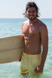 Smiling surfer with surfboard standing at beach coast. Portrait of smiling surfer with surfboard standing at beach coast Royalty Free Stock Photography
