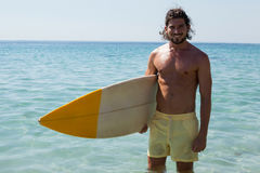 Smiling surfer with surfboard standing at beach coast. Portrait of smiling surfer with surfboard standing at beach coast Royalty Free Stock Photo