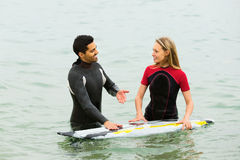 Smiling surfers couple waist deep in water Stock Image