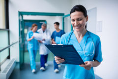 Smiling surgeon holding a clipboard at hospital. Smiling surgeon standing in corridor holding a clipboard at hospital Stock Image