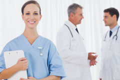 Smiling surgeon posing while doctors talking on background Royalty Free Stock Image