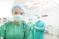Smiling surgeon posing with a team in a surgical room Royalty Free Stock Images