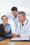 Smiling surgeon working with doctors on computer Royalty Free Stock Image