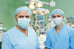 Smiling surgeons team at cardiac surgery operation. Happy surgeons in uniform perform heart transplantation operation on a patient at cardiac surgery clinic royalty free stock photography
