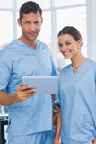 Smiling surgeons working together on tablet Stock Photo