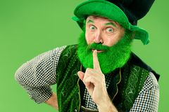 A man in a leprechaun hat at studio. He celebrates St. Patrick`s Day. A smiling surprised happy senior man in a leprechaun hat with beard at green studio. He royalty free stock image