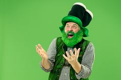 A man in a leprechaun hat at studio. He celebrates St. Patrick`s Day. A smiling surprised happy senior man in a leprechaun hat with beard at green studio. He royalty free stock photo