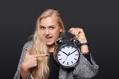 Smiling surprised woman holding alarm clock. And pointing at it, isolated portrait over grey background Royalty Free Stock Photo