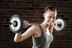 Smiling Sweat beautiful girl lifting dumbbells Royalty Free Stock Photo