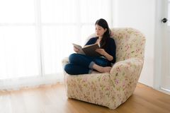 Smiling sweet female model holding history book. Reading information sitting in front of window comfortable sofa on living room at home Royalty Free Stock Photos