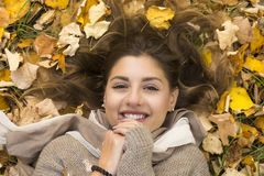 Smiling sweet girl lies down over autumn leaves Royalty Free Stock Photography