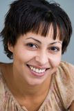 Smiling sweetly. Close up of an happily smiling mulatto woman looking into the camera stock photo
