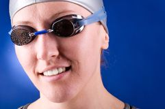 Smiling swimmer. Portrait of a smiling looking at camera woman swimmer on blue background Royalty Free Stock Photo