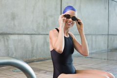 Smiling swimmer sitting at the edge of the swimming pool Stock Photography