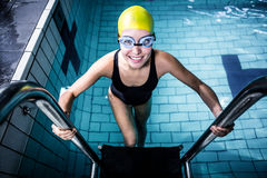 Smiling swimmer woman getting out of the swimming pool Stock Photography