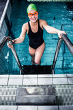 Smiling swimmer woman getting out of the swimming pool Royalty Free Stock Images
