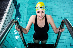 Smiling swimmer woman getting out of the swimming pool Stock Photo