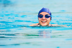 Smiling swimming woman. In blue water. Head of girl in blue water Royalty Free Stock Photo
